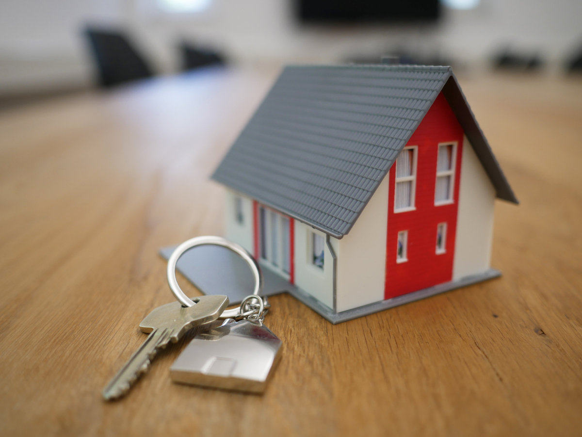 A set of keys next to a small red and white toy house